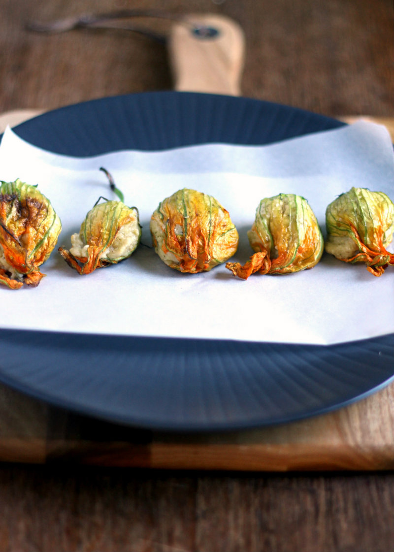 Stuffed and roasted zucchini flowers filled with a creamy vegan cashew cheese filling
